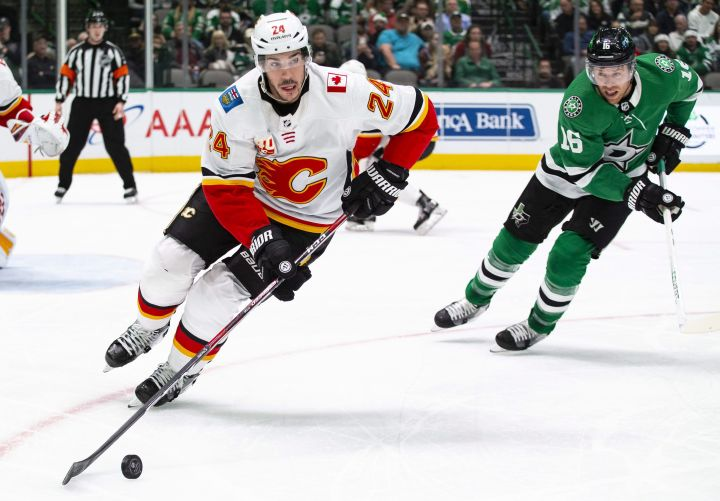 Calgary Flames defenseman Travis Hamonic (24) skates with the puck as Dallas Stars center Joe Pavelski (16) pursues during the first period of an NHL hockey game, Sunday, Dec. 22, 2019, in Dallas.