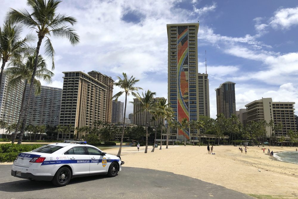 In this March 28, 2020 file photo a police officer arrives at Waikiki Beach in Honolulu.