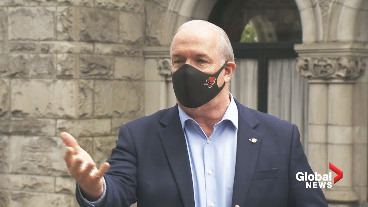 BC NDP leader John Horgan showing how he wears a BC Lions mask during a Global BC Facebook Live.