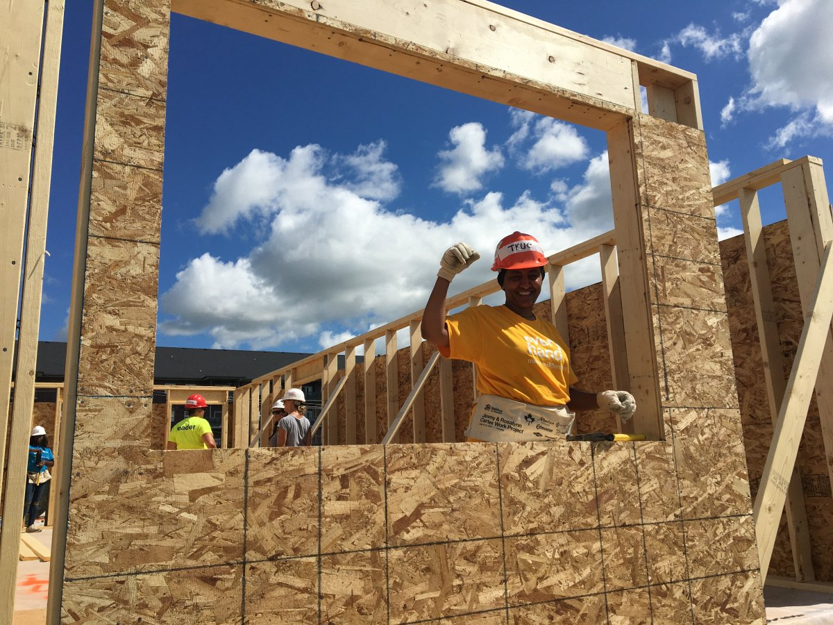 Teruework in the window of her future home thanks to Habitat for Humanity.