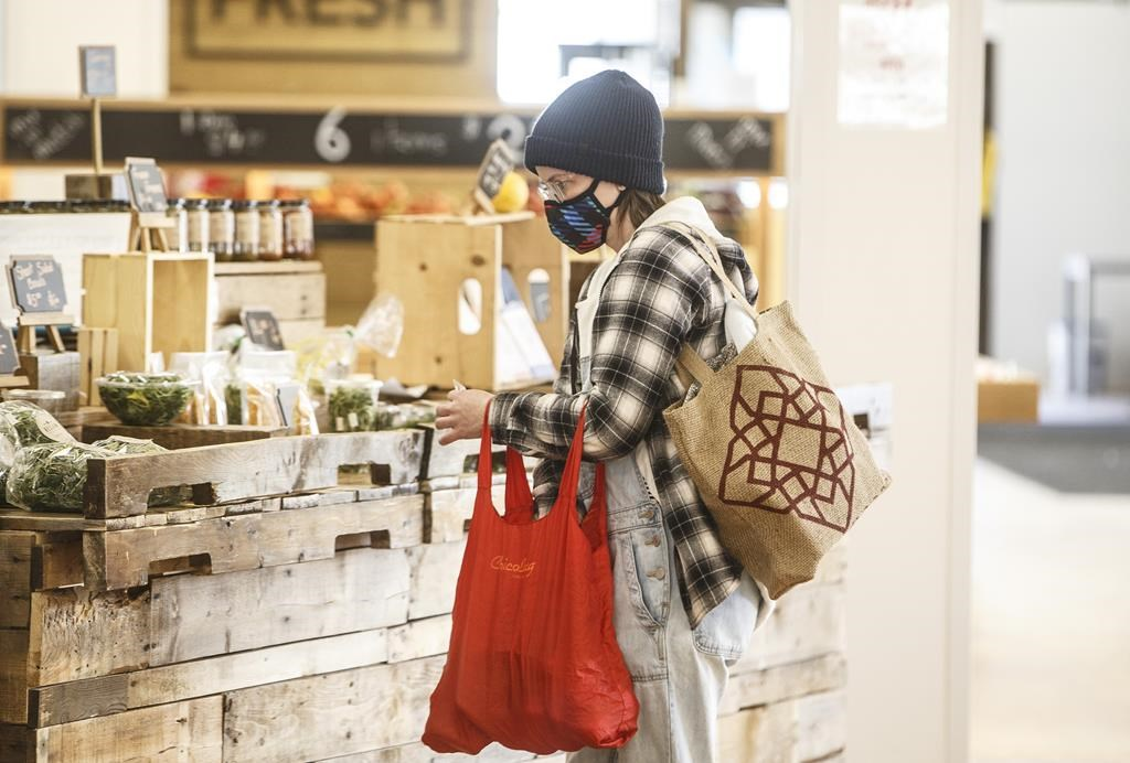 A shopper wearing a mask buys groceries at a sparse farmers market in Edmonton on Sunday March 22, 2020.