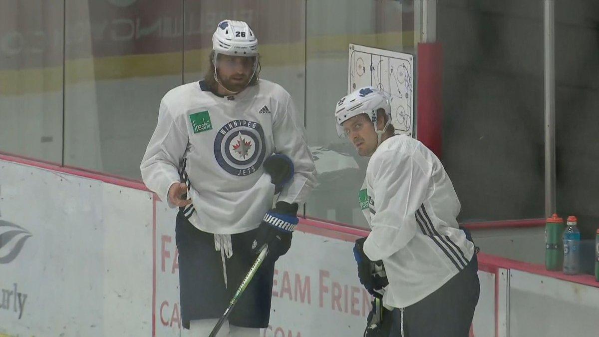 Winnipeg Jets captain Blake Wheeler talks with Mark Scheifele during Tuesday's practice.