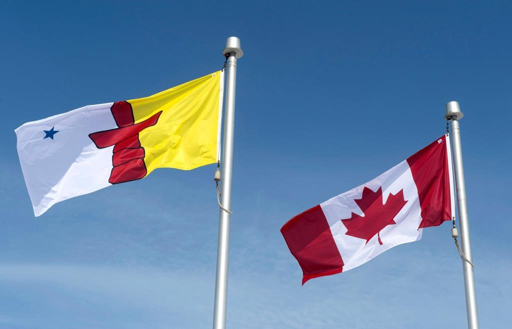 The Nunavut flag and the Canadian flag are seen Saturday, April 25, 2015 in Iqaluit, Nunavut. THE CANADIAN PRESS/Paul Chiasson.