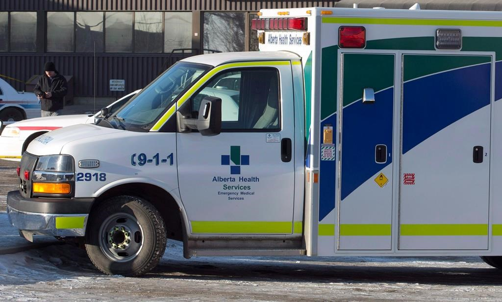 An ambulance waits at the scene as police investigate at a warehouse in Edmonton, on Friday, February 28, 2014. A hospital in west Edmonton has new restrictions in place as the number of COVID-19 cases continues to grow. THE CANADIAN PRESS/Jason Franson.