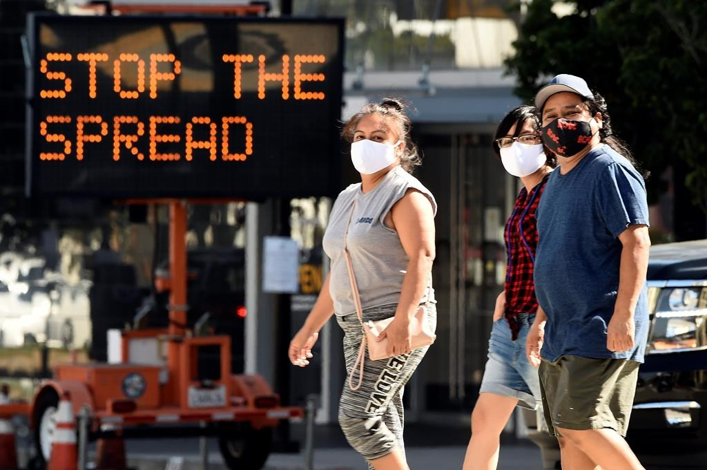 FILE - Pedestrians wear masks as they walk in front of a sign reminding the public to take steps to stop the spread of coronavirus, Thursday, July 23, 2020, in Glendale, Calif.  (AP Photo/Chris Pizzello, File).