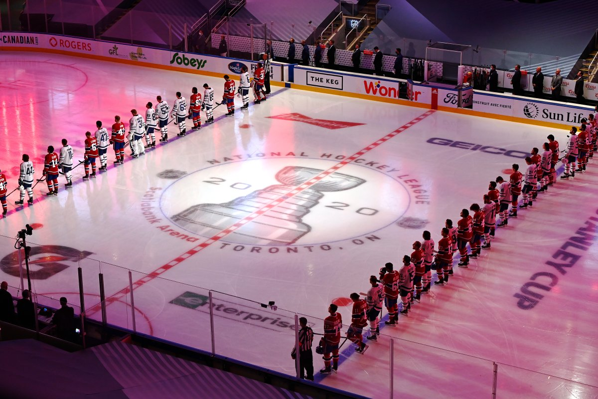 Toronto Maple Leafs and Montreal Canadiens players stand for the Canadian national anthem prior to their NHL exhibition hockey game ahead of the Stanley Cup playoff qualifiers in Toronto on Tuesday, July 28, 2020.