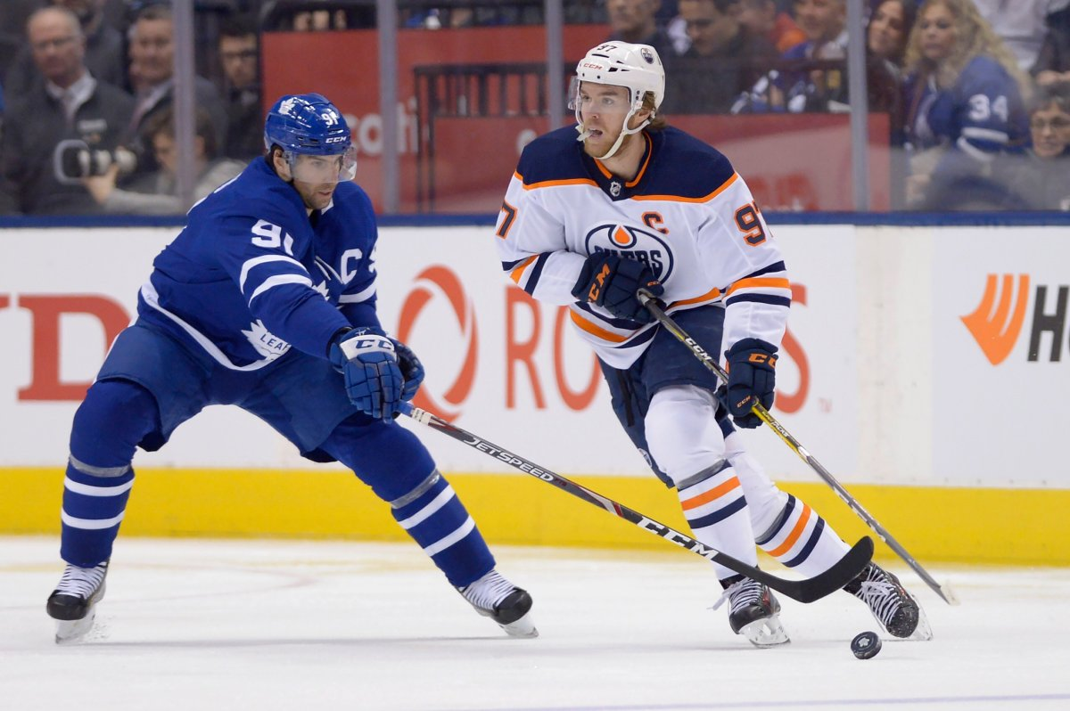 Toronto Maple Leafs centre John Tavares (91) defends as Edmonton Oilers centre Connor McDavid (97) moves with the puck during second period NHL hockey action in Toronto on Jan. 6, 2020.