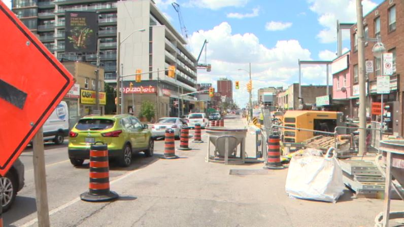 Eglinton Crosstown LRT construction scaffolding and equipment obstructing storefronts at Eglinton and Oakwood avenues.