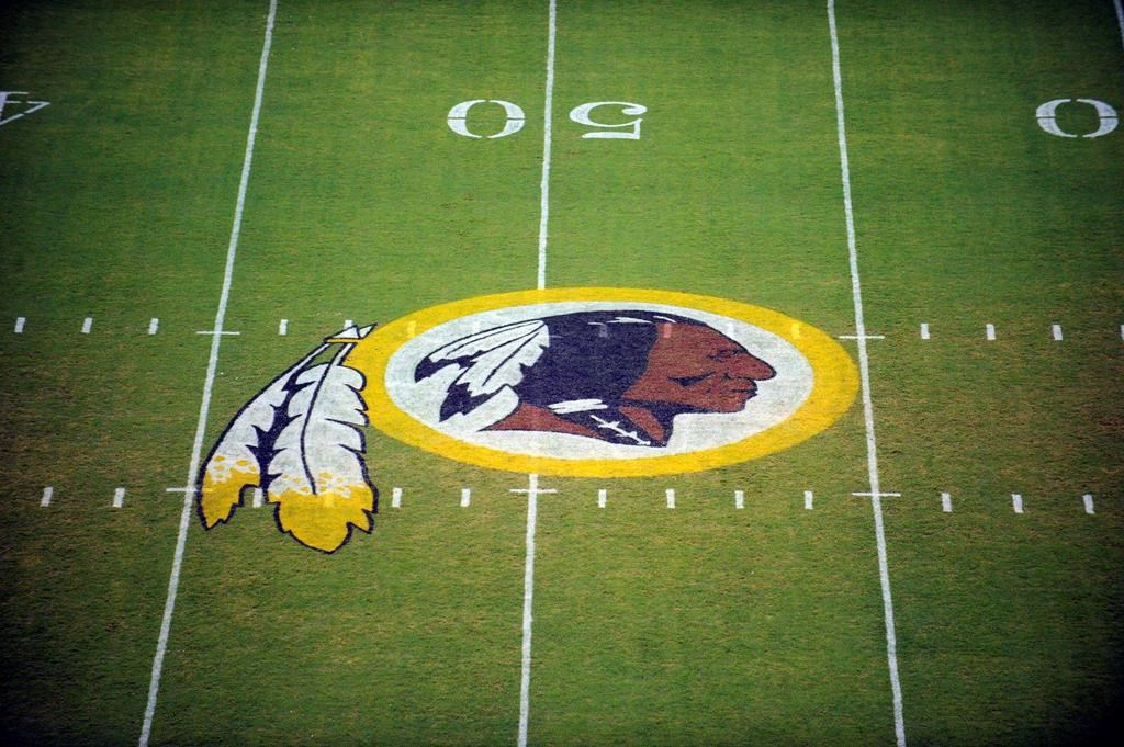 The Washington Redskins logo is shown on the field before the start of a pre-season NFL football game against the New England Patriots in Landover, Md.