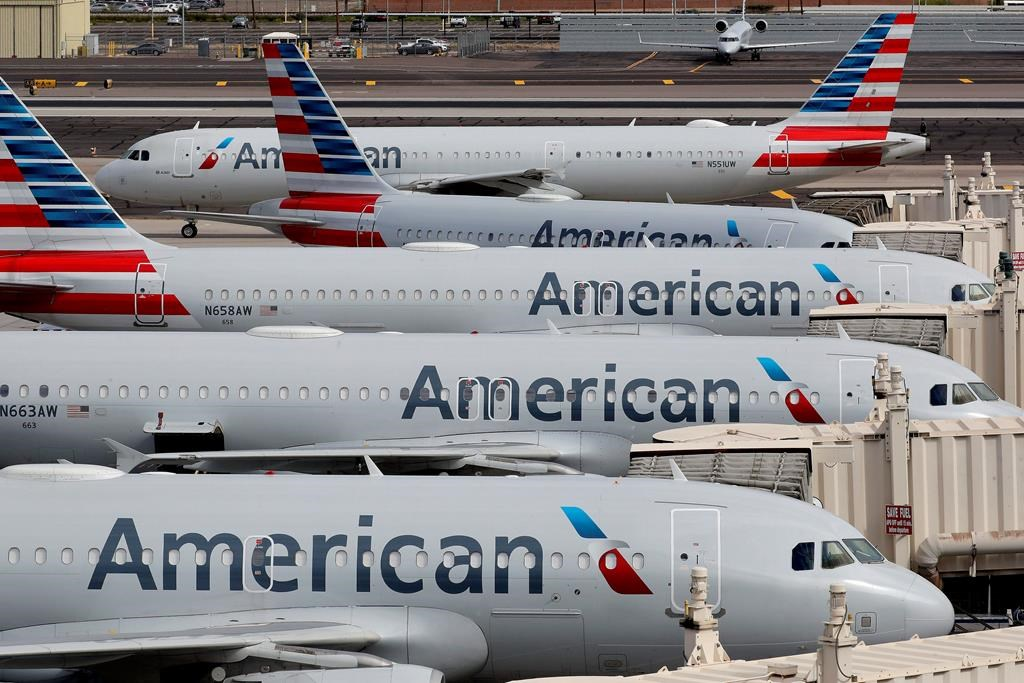 FILE - In this Wednesday, March 25, 2020, file photo, American Airlines jets sit idly at their gates as a jet arrives at Sky Harbor International Airport in Phoenix.