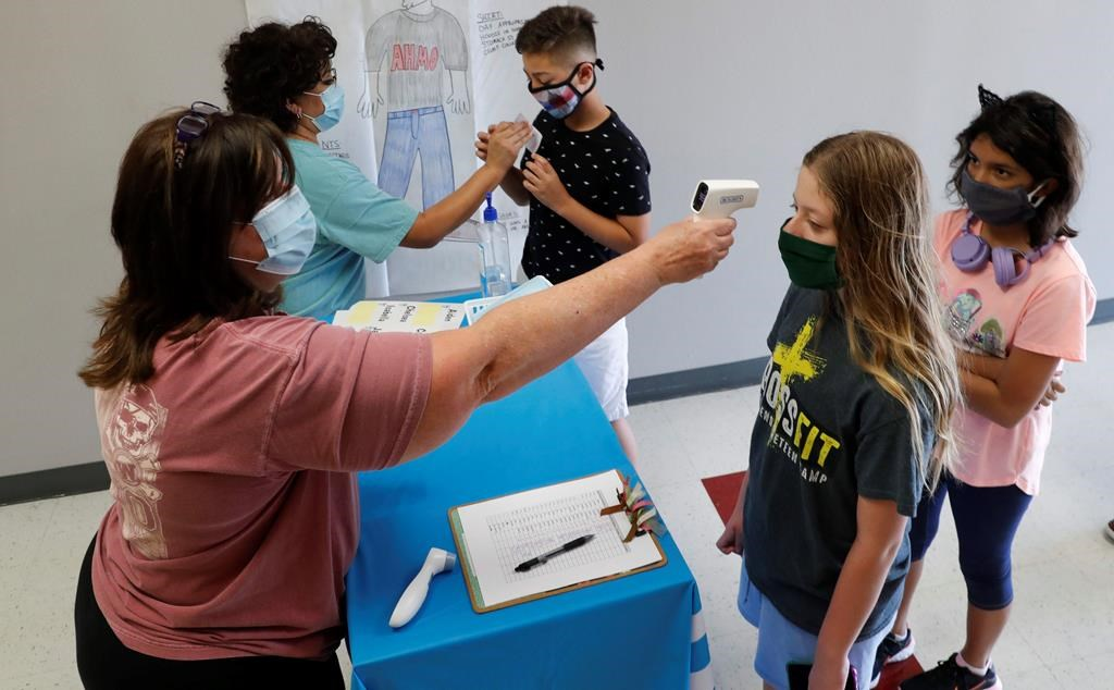 In this Tuesday, July 14, 2020 file photo, teachers check students before a summer STEM camp at Wylie High School in Wylie, Texas.
