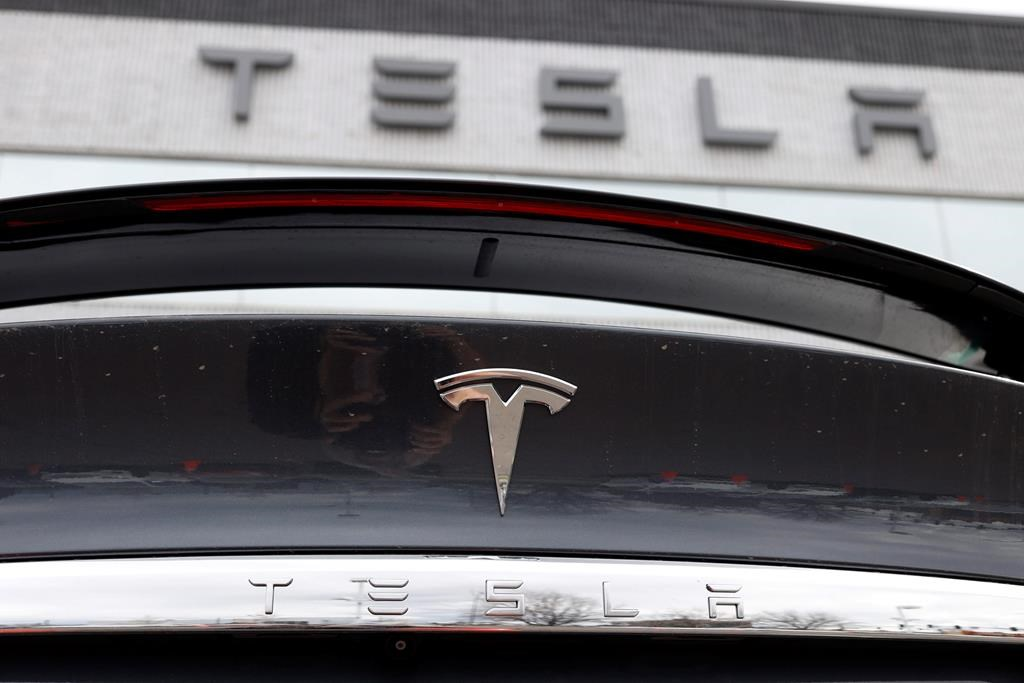 FILE - In this April 26, 2020 photograph, the company logo shines off the rear deck of an unsold 2020 Model X at a Tesla dealership in Littleton, Colo. Tesla is reassuring its 55,000 employees that it hasn't had a major coronavirus outbreak at company facilities worldwide. In an email to workers sent Wednesday, July 15, the company said that since January it has had fewer than 10 cases of the virus that causes COVID-19 that were transmitted in the workplace.(AP Photo/David Zalubowski, File).