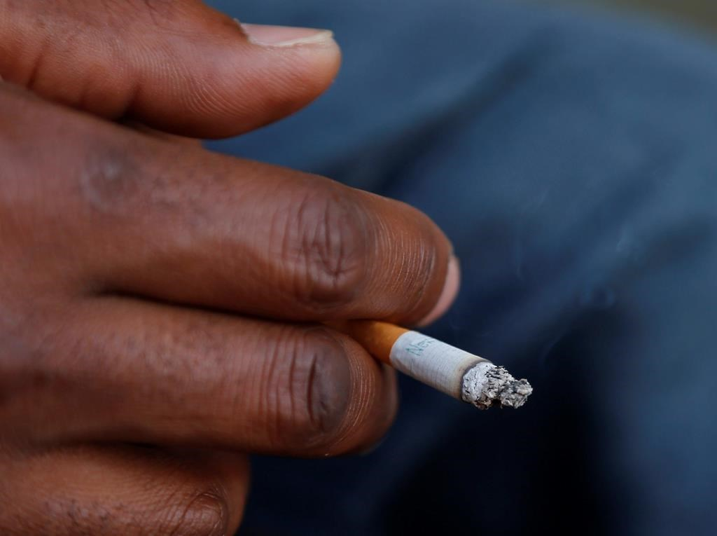 FILE - In this Sept. 17, 2015 file photo, a smoker holds his cigarette outside Oklahoma County Courthouse in Oklahoma City. A federal health panel wants to widen the number of Americans who get yearly scans for lung cancer, by opening the screening to less-heavy smokers. Lung cancer is the nation's top cancer killer, causing more than 135,000 deaths in the U.S. each year. Smoking is the chief cause and quitting is the best protection. (AP Photo/Sue Ogrocki, File).