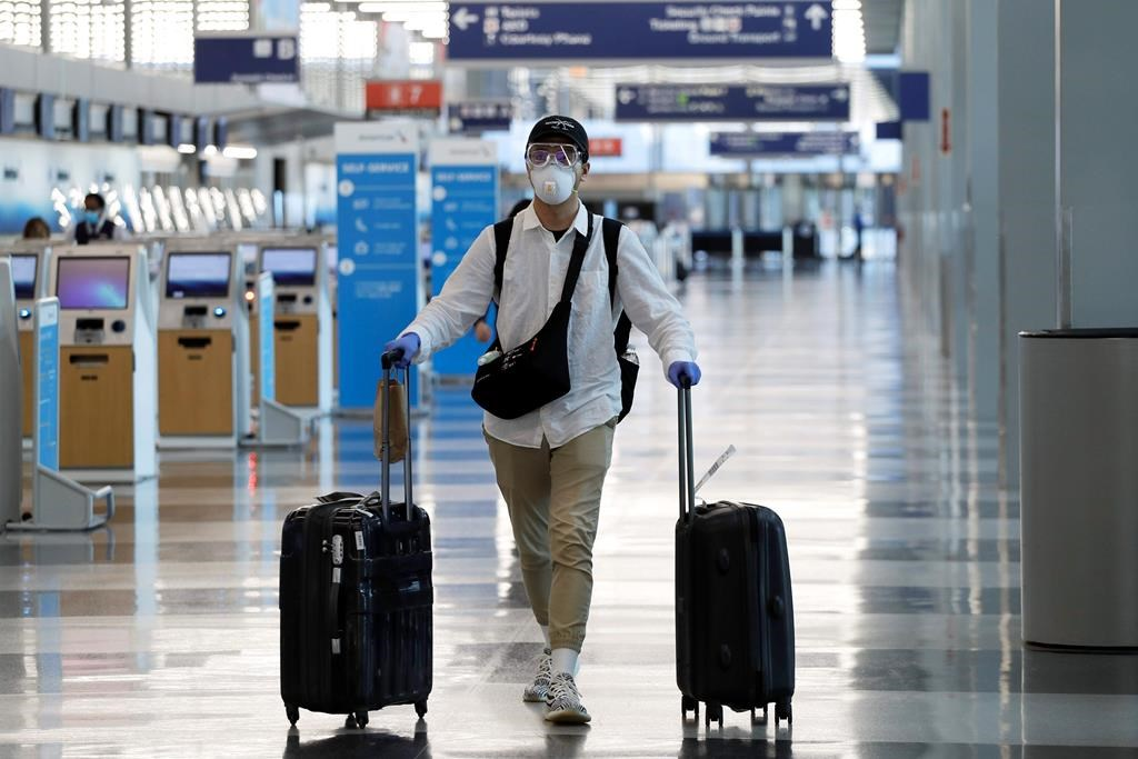 FILE - In this June 16, 2020 file photo, a traveler wears a mask and protective goggles as he walks through Terminal 3 at O'Hare International Airport in Chicago. United Airlines says its face mask requirement now extends to ticket counters and airport lounges. United said Wednesday, July 22 that it might ban violators from flying on its planes. United and all other major U.S. airlines already require passengers to wear masks during flights. (AP Photo/Nam Y. Huh, File).