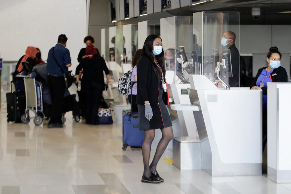 Ticket agents wear protective masks during the coronavirus pandemic while helping travelers at LaGuardia Airport, Wednesday, July 15, 2020, in New York.