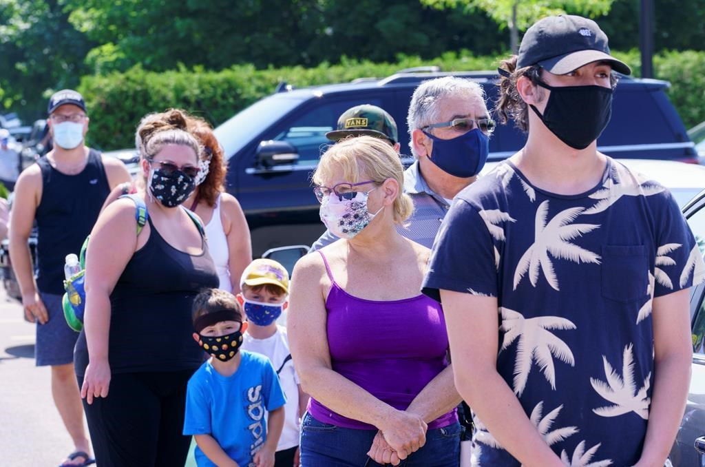 People line up to enter a mobile COVID-19 test clinic in Mercier, Que., Thursday, July 9, 2020. A small community south of Montreal is making mask-wearing mandatory beginning today inside all commercial businesses following a COVID-19 outbreak authorities say is tied to a house party.THE CANADIAN PRESS/Paul Chiasson.