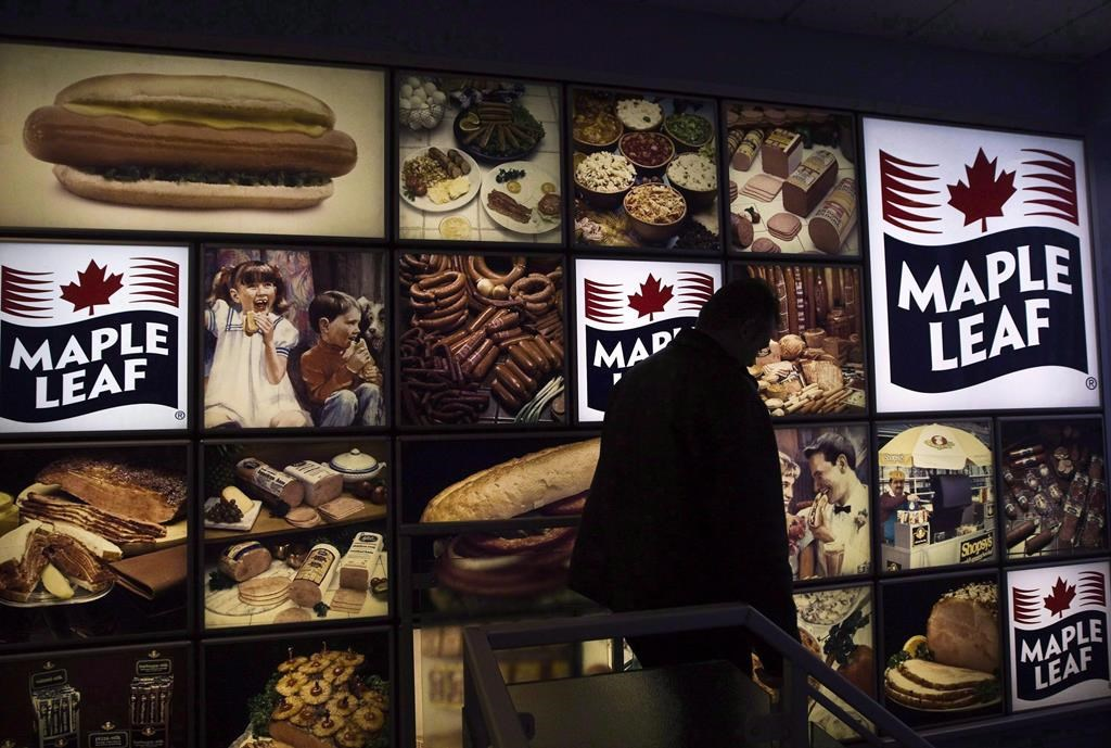 A Maple Leaf Foods employee walks past a Maple Leaf sign at the company's meat facility in Toronto. The company confirmed Wednesday an employee at its Brandon plant has tested positive for COVID-19.