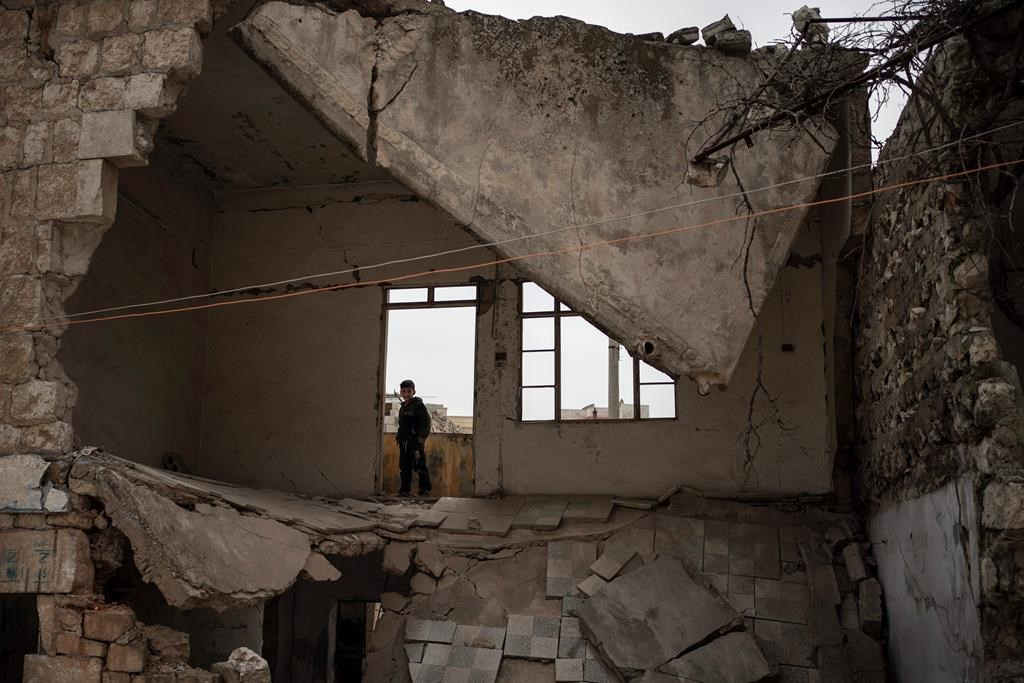 In this Thursday, March 12, 2020 photo, a boy stands inside a house destroyed by an airstrike, in Idlib, Syria.