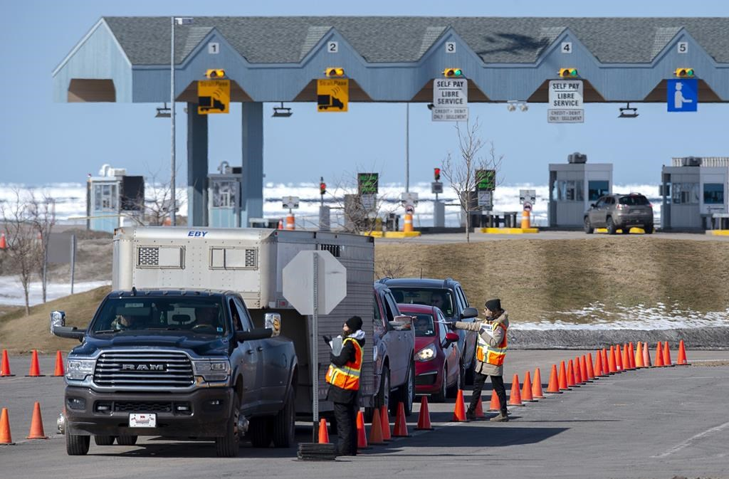 Provincial health department workers stop traffic that has crossed the Confederation Bridge in Borden-Carleton, P.E.I. on Sunday, March 22, 2020. Atlantic Canadian provinces will lift travel restrictions within the region starting tomorrow, with some identification from visitors required. THE CANADIAN PRESS/Andrew Vaughan.