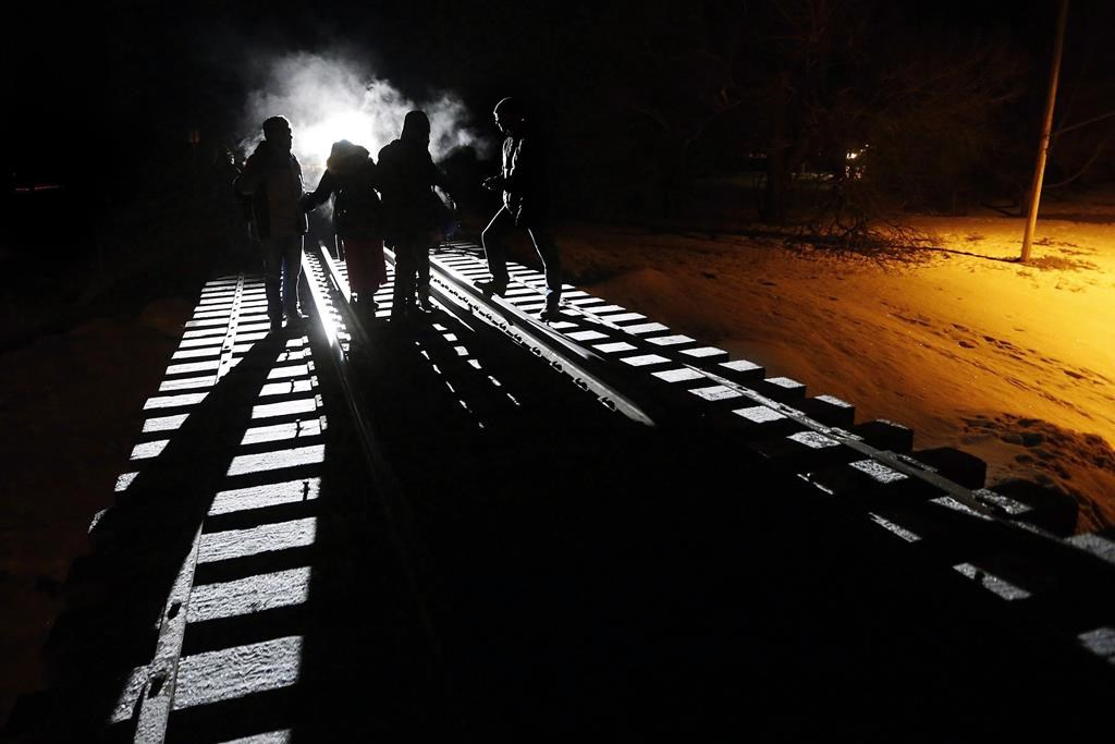 Migrants from Somalia cross into Canada illegally from the United States by walking down a train track into the town of Emerson, Man., on Feb.26, 2017. A federal judge has struck down a key agreement on refugees between Canada and the United States. In a ruling today, Federal Court Justice Ann Marie McDonald says elements of the law underpinning the Safe Third Country Agreement violate constitutional guarantees of life, liberty and security.