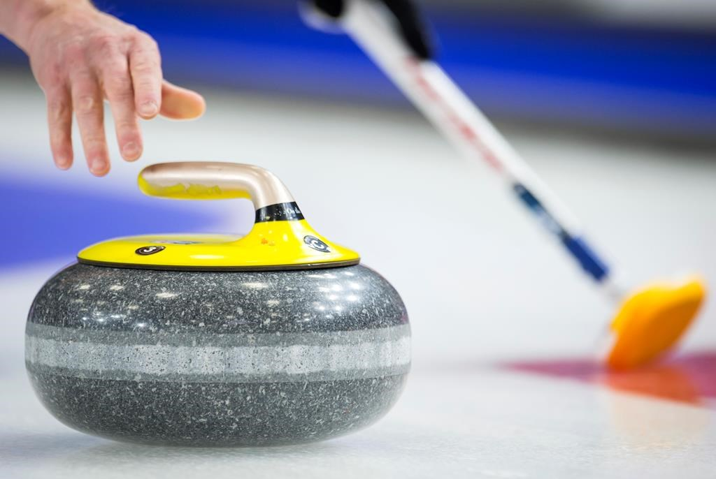 A curler releases a rock during play at the 2019 Brier.