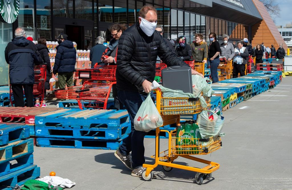 Long lines of masked shoppers wait to shop for groceries in Toronto on Thursday, April 9, 2020.
