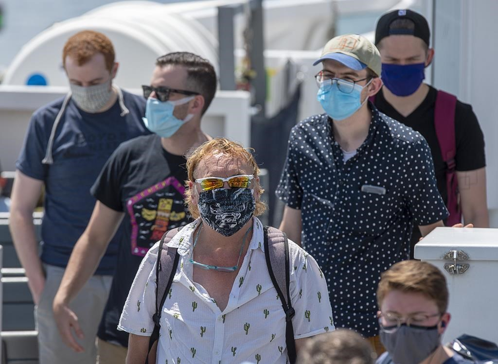 Passengers wear face masks on a Halifax Transit ferry as it arrives in Dartmouth, N.S. on Friday, July 24, 2020.