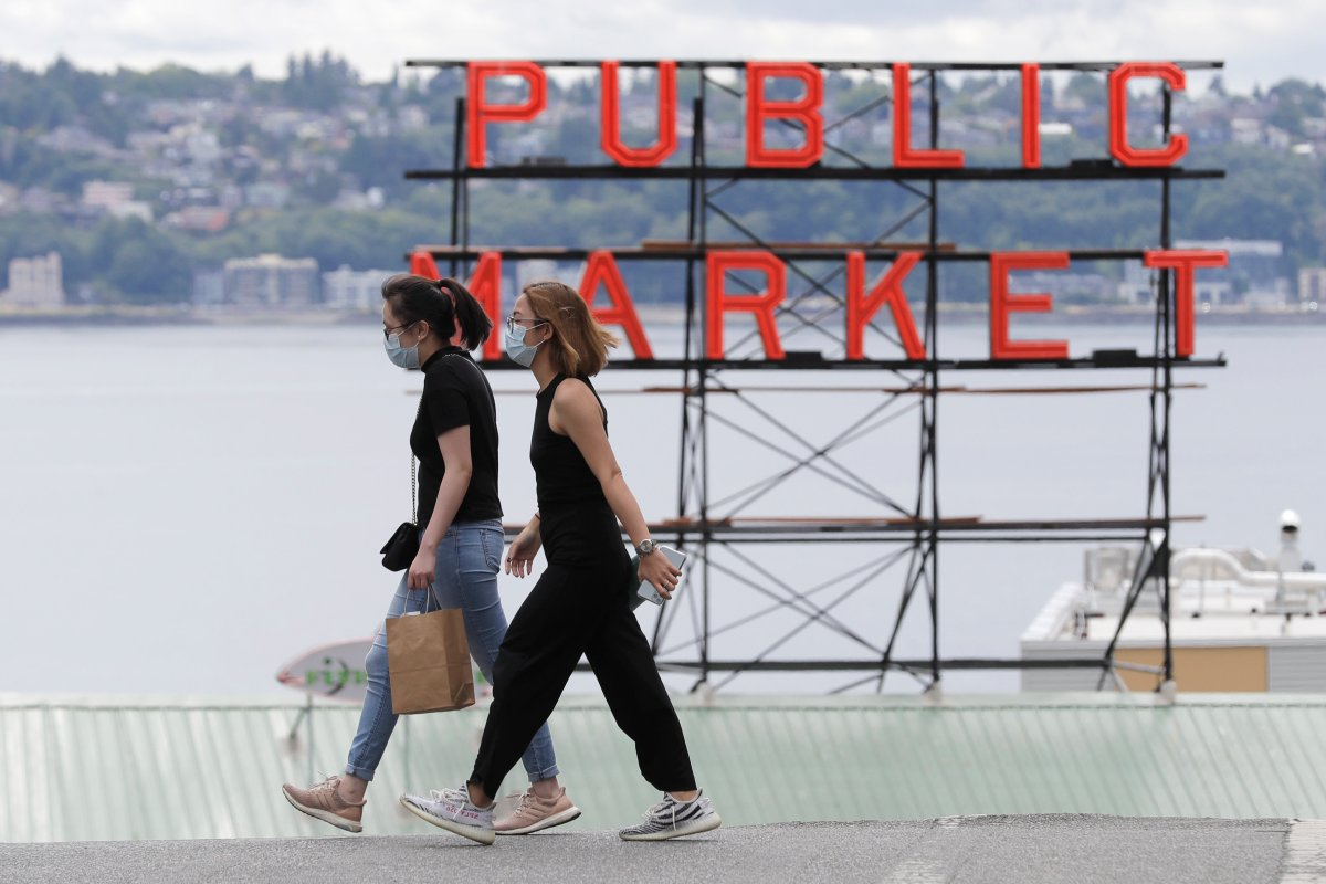 People wear masks as they cross a street Tuesday, July 7, 2020, near a sign for the Pike Place Market in Seattle.