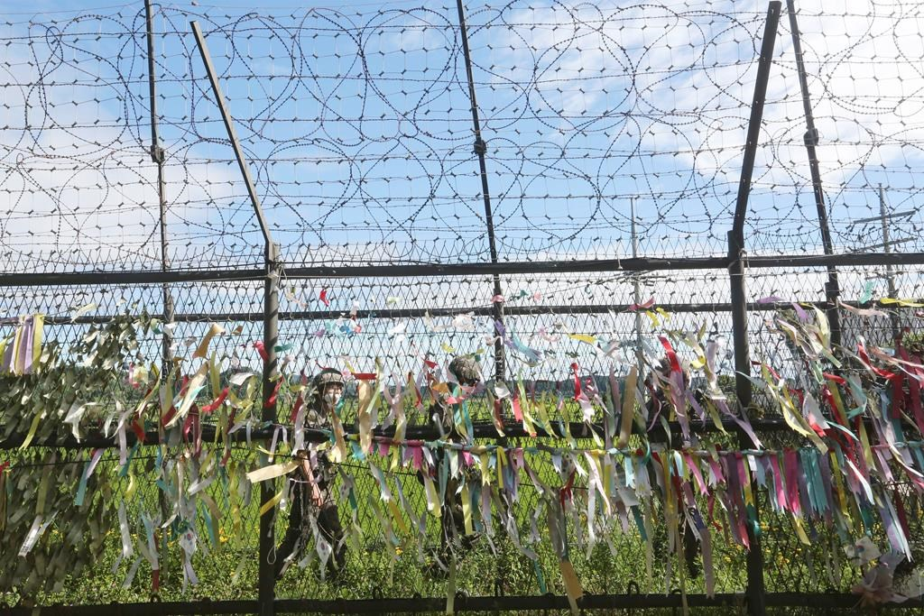 """South Korean army soldiers wearing face masks to help protect against the spread of the new coronavirus pass by a wire fence decorated with ribbons written with messages wishing for the reunification of the two Koreas at the Imjingak Pavilion in Paju, near the border with North Korea, Sunday, July 26, 2020. North Korean leader Kim Jong Un placed the city of Kaesong near the border with South Korea under total lockdown after a person was found with suspected COVID-19 symptoms, saying he believes """"the vicious virus"""" may have entered the country, state media reported Sunday."""