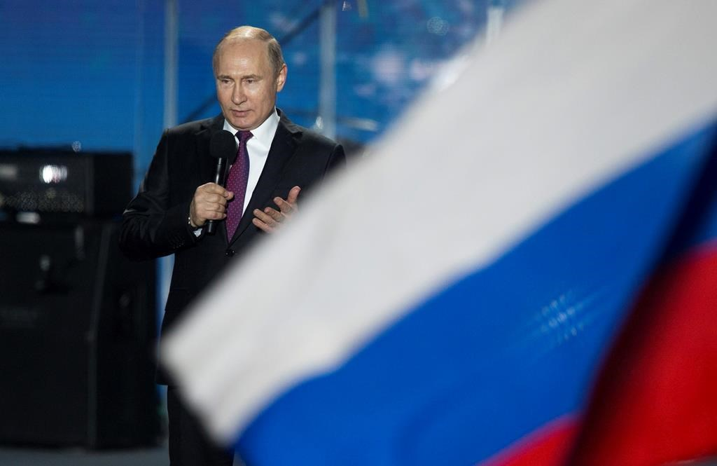 FILE - In this file photo dated Wednesday, March 14, 2018, Russian President Vladimir Putin speaks in front of a Russian National flag in Sevastopol, Crimea.