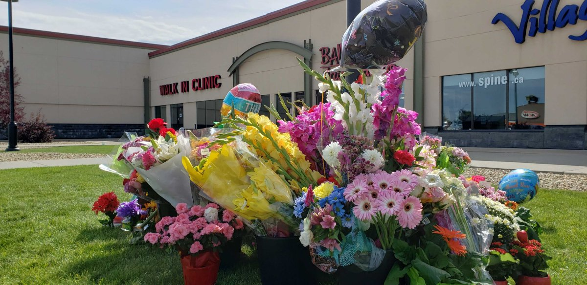 Flowers and messages are left outside the Village Mall Walk-In Clinic in Red Deer Aug. 14, 2020, to honour Dr. Walter Reynolds.