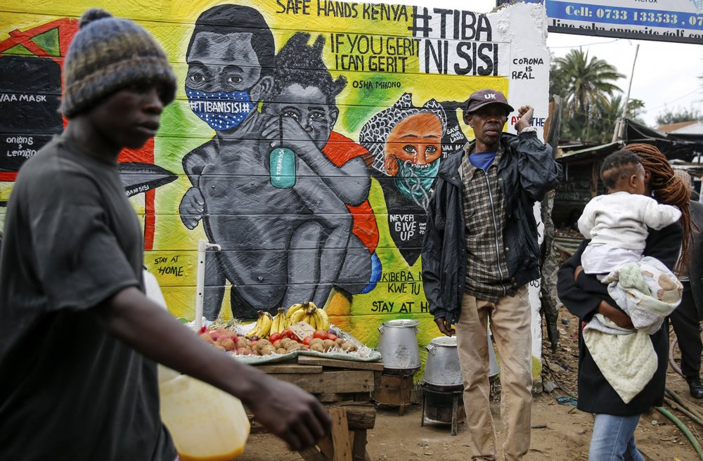 "FILE - In this July 8, 2020, file photo, people walk past an informational mural warning people about the dangers of the new coronavirus and how to prevent transmission, with words in Swahili reading ""We are the Cure"", painted by youth artists from the Uweza Foundation, in the Kibera slum, or informal settlement, of Nairobi, Kenya. A dangerous stigma has sprung up around the coronavirus in Africa — fueled, in part, by severe quarantine rules in some countries as well as insufficient information about the virus."