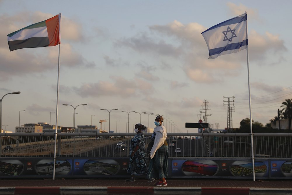 Women wearing face masks against the coronavirus walk past United Arab Emirates and Israeli flags at the Peace Bridge in Netanya, Israel, Sunday, Aug. 16, 2020. The UAE flag was displayed to celebrate last week's announcement that Israel and the United Arab Emirates have agreed to establish full diplomatic relations.