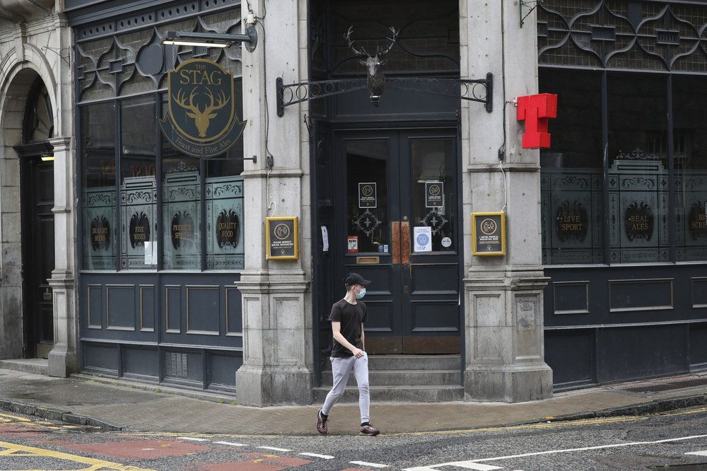 A man walks past the closed Stag pub, after bars, cafes and restaurants were ordered to close as lockdown restrictions were reimposed due to a coronavirus cluster in the area, in Aberdeen, Scotland, Wednesday, Aug. 5, 2020. A five-mile travel rule has been put in place and residents are being told not to enter each other's houses as First Minister Nicola Sturgeon said over 50 cases have now been reported.