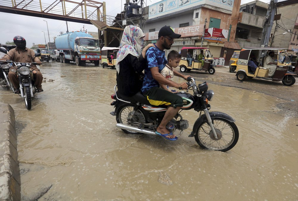 Motorcyclists drive through a road flooded by heavy rainfall in Karachi, Pakistan, Sunday, Aug. 9, 2020. Three days of heavy monsoon rains triggering flash floods killed at least dozens people in various parts of Pakistan, as troops with boats rushed to a flood-affected district in the country's southern Sindh province Sunday to evacuate people to safer places.
