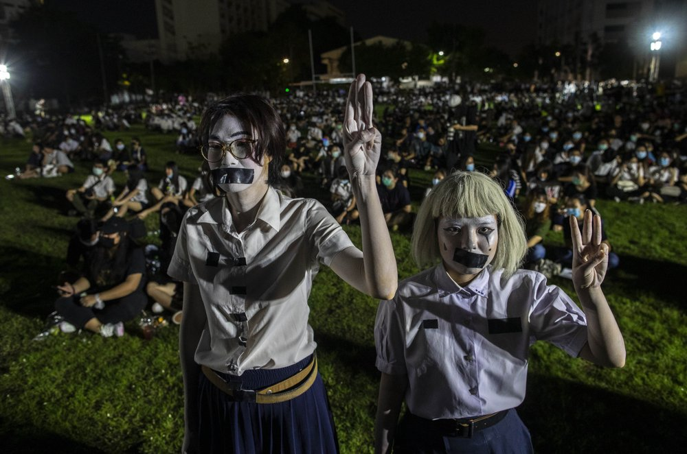 Pro-democracy students with tape covering their mouths raise a three-finger salute, a symbol of resistance, during a protest rally at Mahidol University in Nakhan Pathom, Thailand, Tuesday, Aug. 18, 2020. Student protesters have stepped up pressure on the government with three core demands: holding new elections, amending the constitution and ending the intimidation of critics of the government.