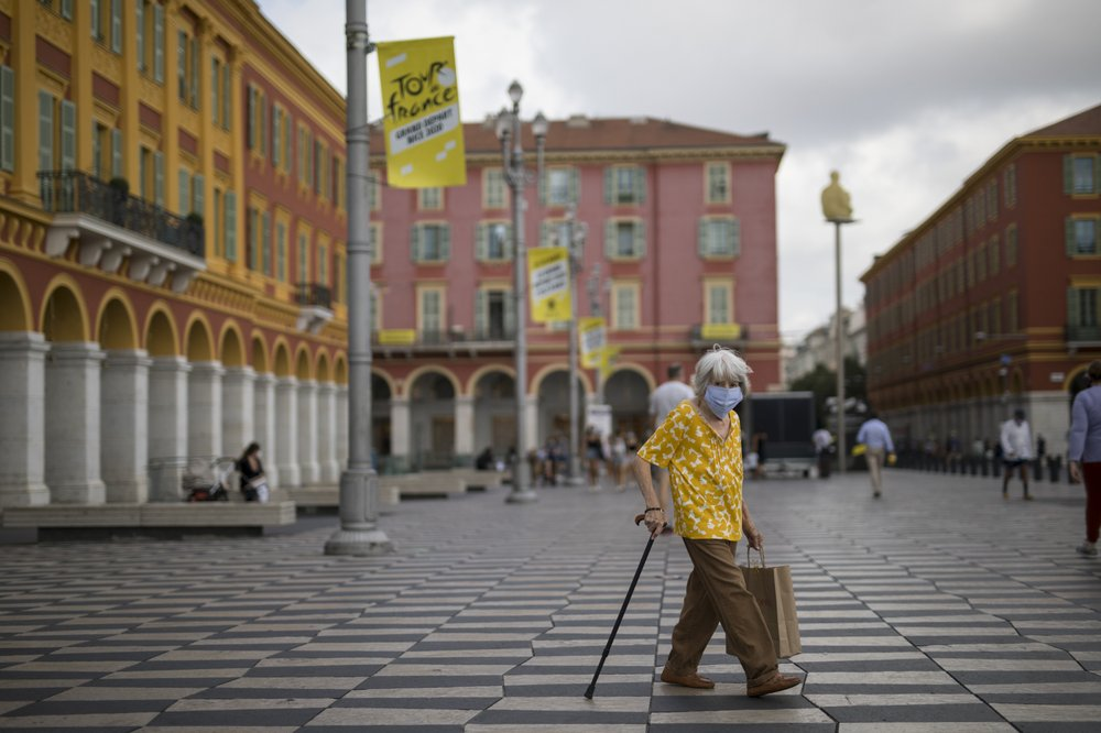 A woman wearing a mask to protect against the coronavirus walks through the Place Massena in Nice, southern France, Friday, Aug 28, 2020. The Tour de France sets off Saturday Aug. 29, shrouded in uncertainty in the face of the coronavirus pandemic and mounting infections in France.