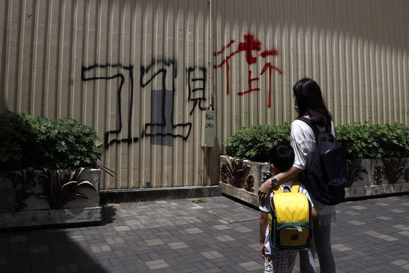 """Pamela Lam and her son stand in Hong Kong, Friday, July 3, 2020. Lam's 6-year-old son fell in love with the Hong Kong protest anthem, """"Glory to Hong Kong,"""" the first time he heard it and sings it quite often. The Chinese painted on wall reads: """"See you on street at July 1."""" Lam agreed to be photographed only if her face was not shown, fearing possible retribution from authorities."""