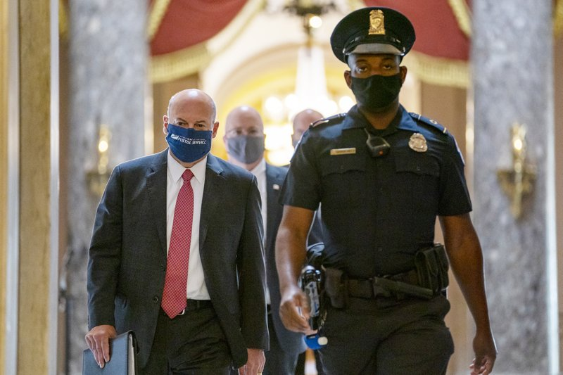 Postmaster General Louis DeJoy, left, is escorted to House Speaker Nancy Pelosi's office on Capitol Hill in Washington, Wednesday, Aug. 5, 2020. Facing public backlash, DeJoy is set to testify Friday about disruptions in mail delivery.