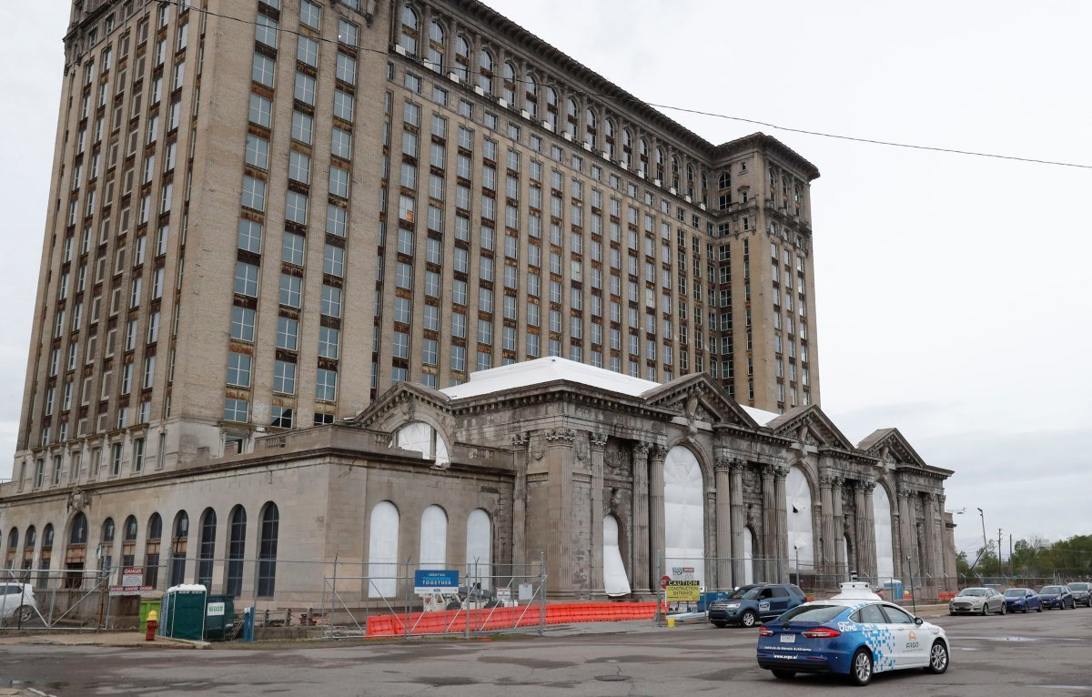 FILE - A Ford autonomous car drives by the Michigan Central train depot, Thursday, May 23, 2019, in Detroit.
