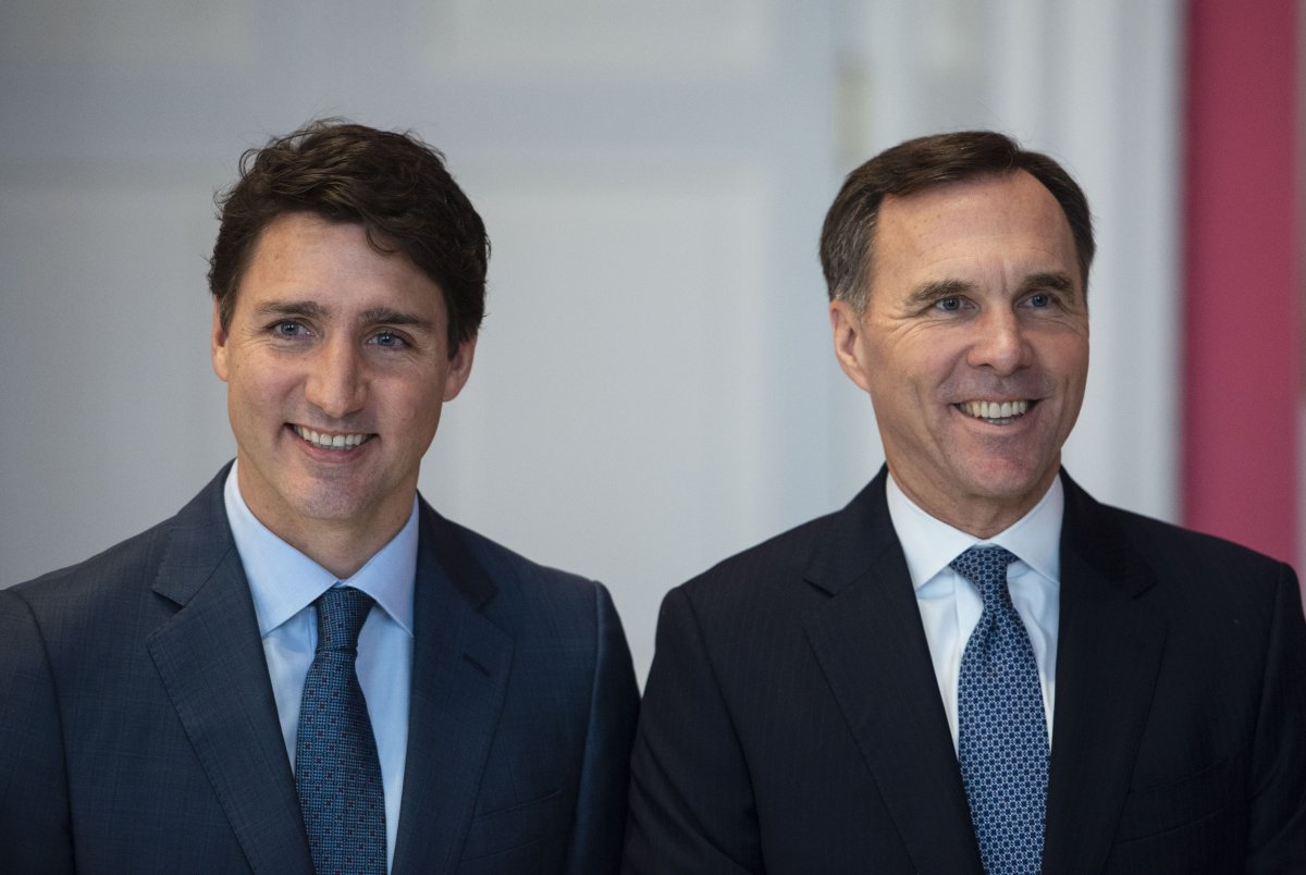 Prime Minister Justin Trudeau stands with Bill Morneau as he remains Minister of Finance during the swearing in of the cabinet at Rideau Hall in Ottawa in a Nov. 20, 2019, file photo.