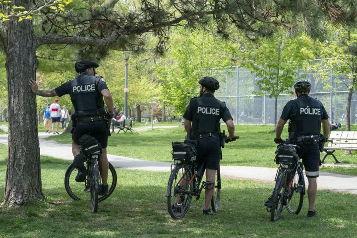 Bicycle police officers keep an eye on Trinity Bellwoods Park in Toronto on Sunday, May 24, 2020.