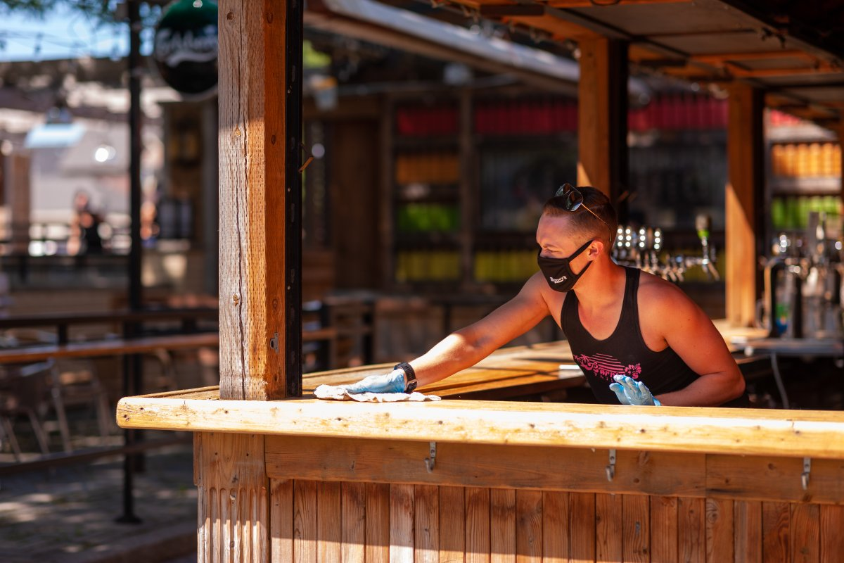 A worker at Barney's patio on Richmond Street in London, Ont., cleans the bar on June 12, 2020.