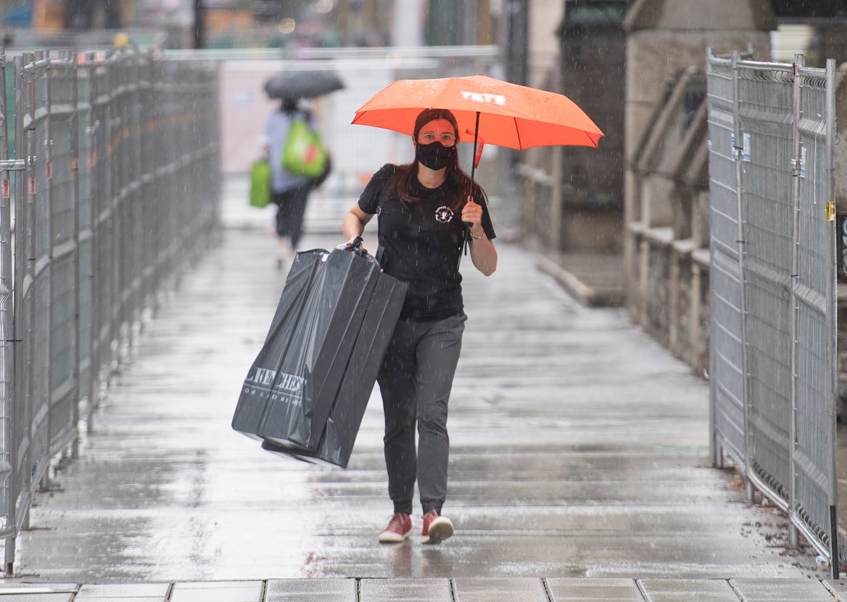 A woman wears a face mask as she walks in the rain in Montreal, Sunday, August 2, 2020, as the COVID-19 pandemic continues in Canada and around the world.