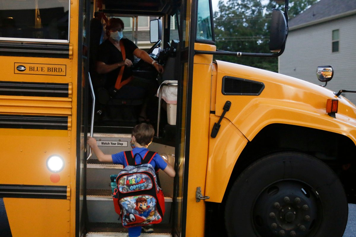 Paul Adamus, 7, climbs the stairs of a bus before the fist day of school on Monday, Aug. 3, 2020, in Dallas, Ga.