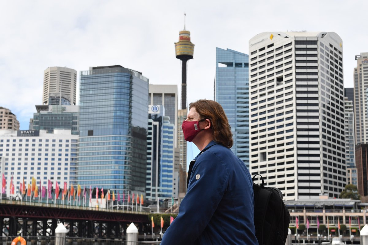 epa08583077 A pedestrian wearing a face mask at Darling Harbour in Sydney, New South Wales (NSW), Australia, 04 August 2020. NSW Premier Gladys Berejiklian said it was 'strongly recommended' that people wear masks from Monday in enclosed spaces (such as public transport), if they work in a customer-facing role (such as hospitality or retail), if they attend a place of worship, or if they are in an area where there is high community transmission.