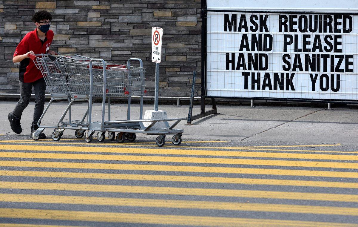 A staff member wears a mask as he collects carts at a store in Ottawa, on Saturday, Aug. 1, 2020, in the midst of the COVID-19 pandemic.