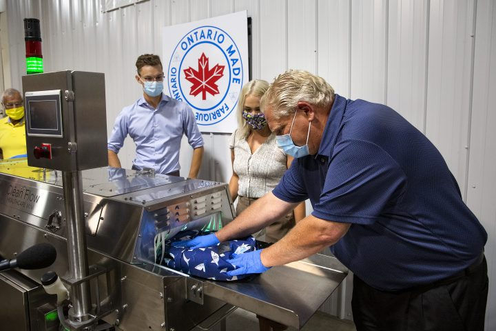 Ontario Premier Doug Ford pushes a children's backpack through a sanitization machine at Clean Works Corp. in Beamsville, Ont., on Tuesday, Aug. 4, 2020.