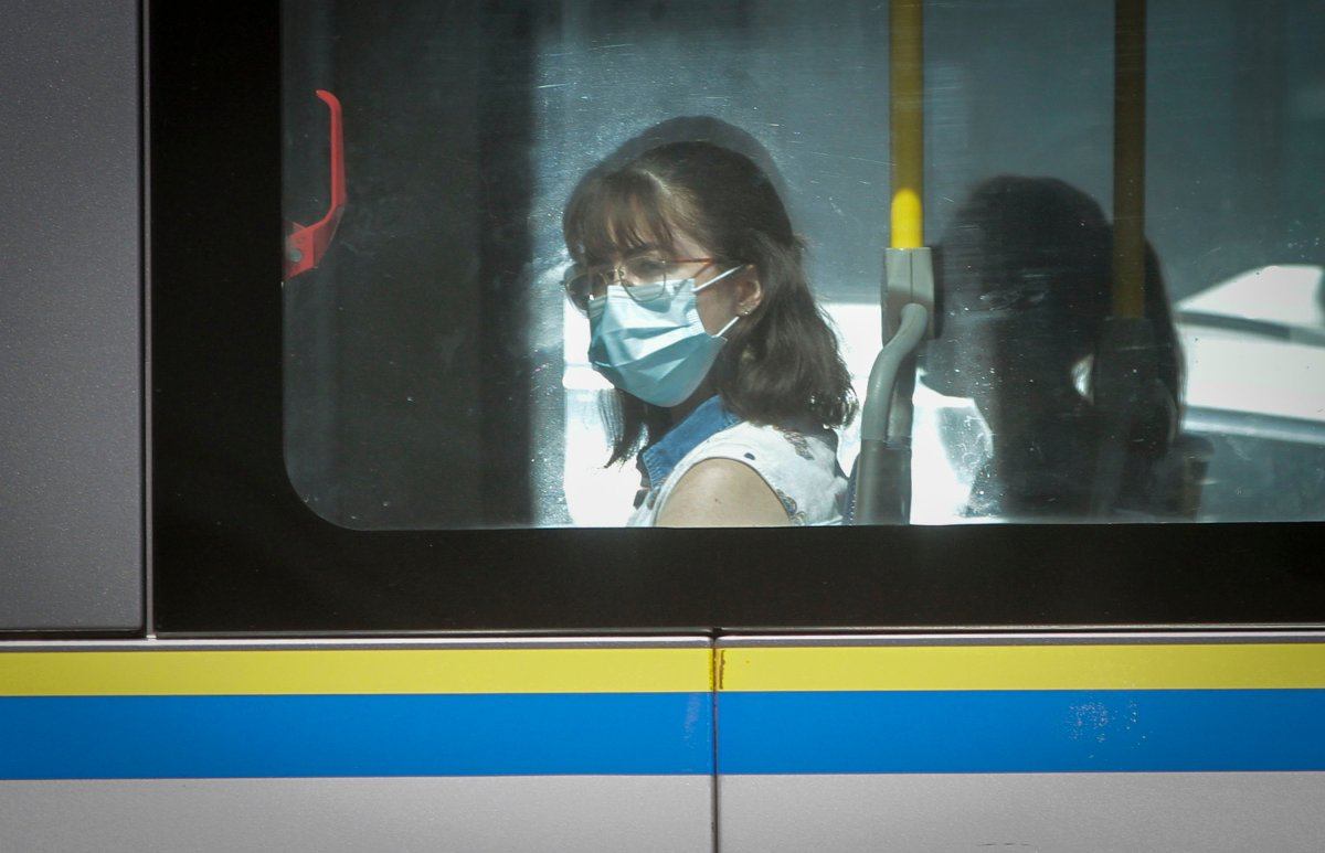 A woman wearing a face mask is seen on a bus in Vancouver, British Columbia, Canada, Aug 4, 2020. The British Columbia Provincial health officer asked the public transit authorities to implement a mandatory mask policy like some other provinces in Canada. In Regina, the city is requiring all people who are riding public transit to wear a mask. The new rules comes into effect on Friday, Aug. 21.