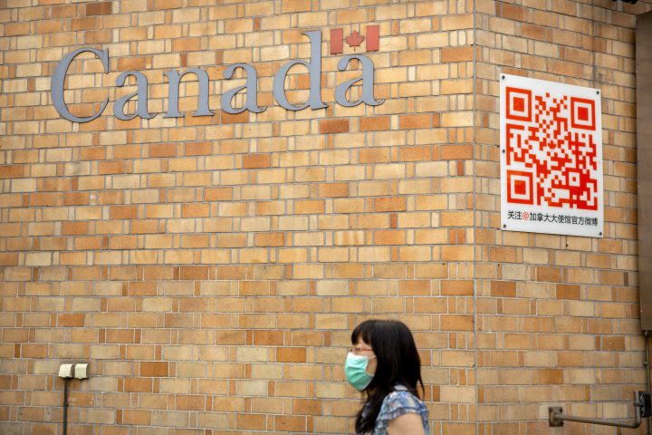 A woman wearing a face mask to help protect against the coronavirus walks past the Canadian Embassy in Beijing, Thursday, Aug. 6, 2020.